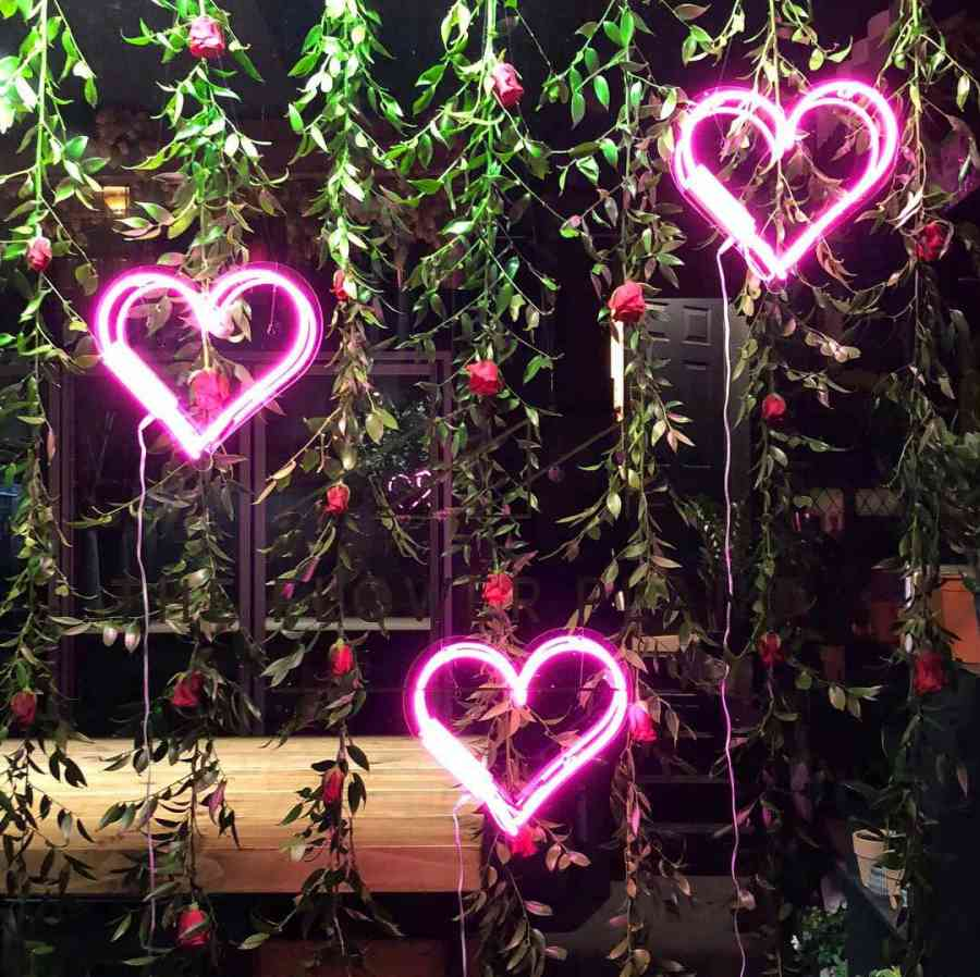 Pink neon hearts and hanging red roses
