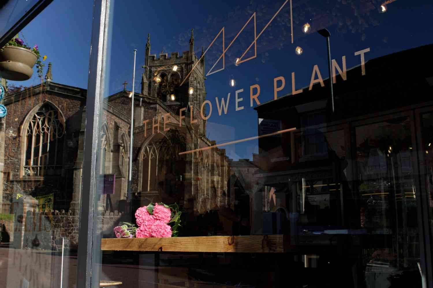 The Flower Plant florist window with reflection of St Mary's Church