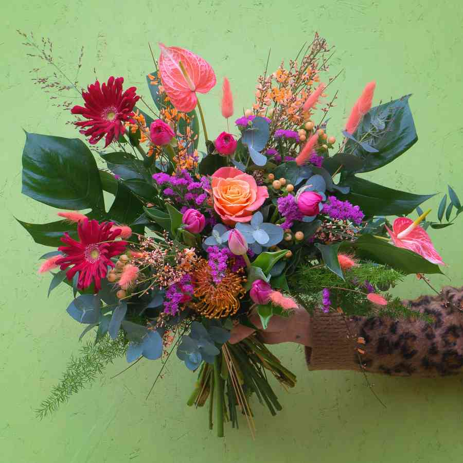 Roses, ranunculus, limonium, genista, anthurium, grasses and textured foliage