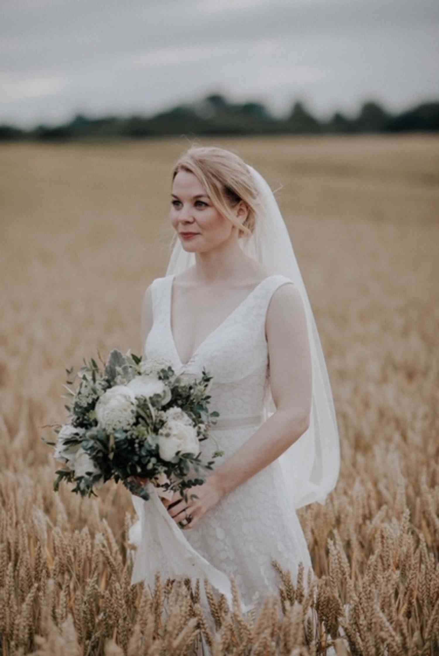 Bride standing in wheat field with white bridal bouquet